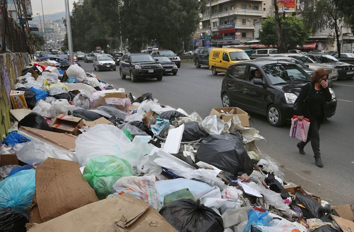 In this Thursday, Dec. 17, 2015 photo, a Lebanese woman covers her nose from the smell as she passes by a pile of garbage on a street in Beirut, Lebanon. Lebanon's trash collection crisis which set off summer protests is entering its sixth month, but you would hardly be able to know it in Beirut. (AP Photo/Bilal Hussein) ORG XMIT: XBH506